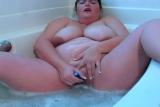 Plnoštíhlá žena masturbuje ve vaně