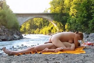 Amatérský pár prcá na dece na břehu řeky