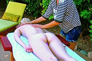 Blonde girl is enjoying relaxing massage in the garden