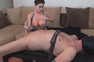 Oiled domina Emmanuelle London jerks off a tied up guy